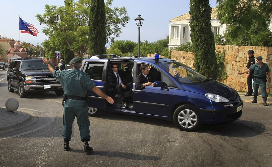 Security officers escort a convoy of cars, one believed to be transporting first lady Michelle Obama on arrival at the Villa Padierna Hotel in Marbella, southern Spain, Wednesday, Aug. 4, 2010. The White House says Mrs. Obama is in Spain for a private trip with longtime family friends. (AP Photo/Sergio Torres)