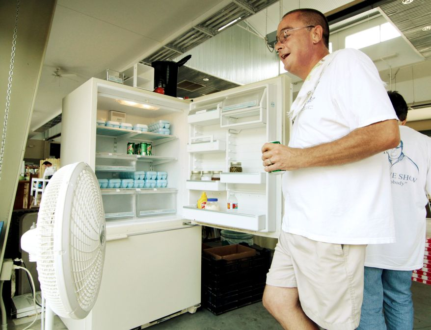 ASSOCIATED PRESS Bob Stoltzfus cools down with a fan and cool air escaping from a refrigerator while taking inventory of his egg supply at the Mississippi Farmers Market in Jackson, Miss., on Thursday.