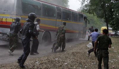 Kyrgyz government forces stop a bus with supporters of former presidential hopeful Urmat Baryktabasov who gathered on a highway some 9 miles east of the capital, Bishkek, on Thursday, Aug. 5, 2010, to demand the resignation of the government. The government forces used tear gas and stun grenades to disperse hundreds of protesters, raising fears of new instability in the turbulent Central Asian nation. (AP Photo)