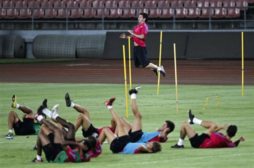 Spain's soccer club FC Barcelona's Lionel Messi, left, stretches his legs while the team's head coach Josep Guardiola prepares to kick a ball during a training for the match against China's Beijing Guoan club at the Worker's Stadium in Beijing Thursday, Aug. 5, 2010. FC Barcelona will play a friendly against Chinese champions Beijing Guoan at China's National Stadium, also known as the Bird's Nest, on Sunday, Aug. 8, 2010. (AP Photo/Alexander F. Yuan)