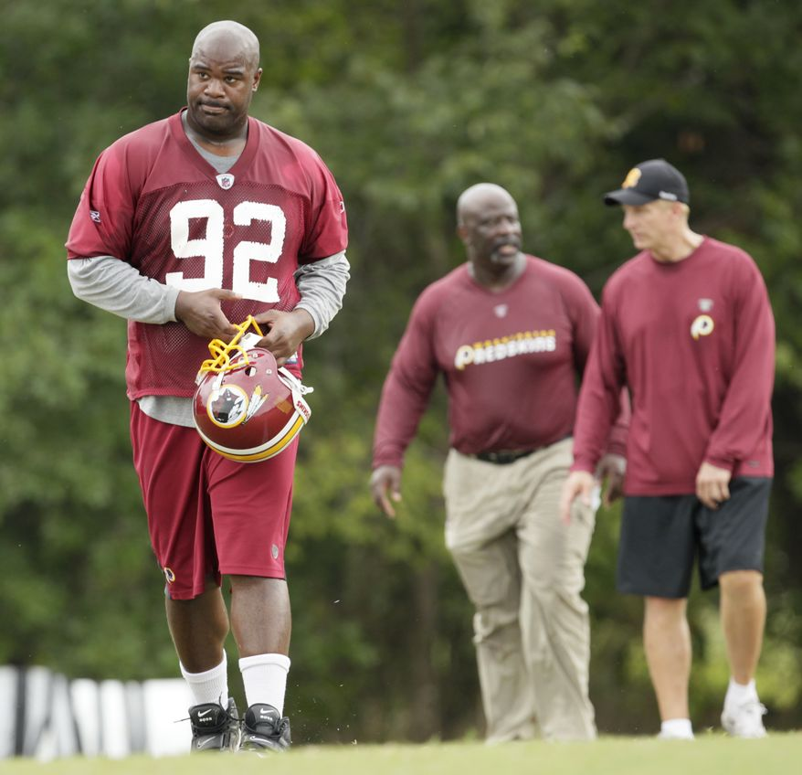 ASSOCIATED PRESS Washington Redskins' Albert Haynesworth, left, walks from the field after training with defensive line coach Jacob Burney, center, and defensive coordinator Jim Haslett at the NFL football team's training camp at Redskins Park, Thursday, Aug. 5, 2010, in Ashburn, Va.