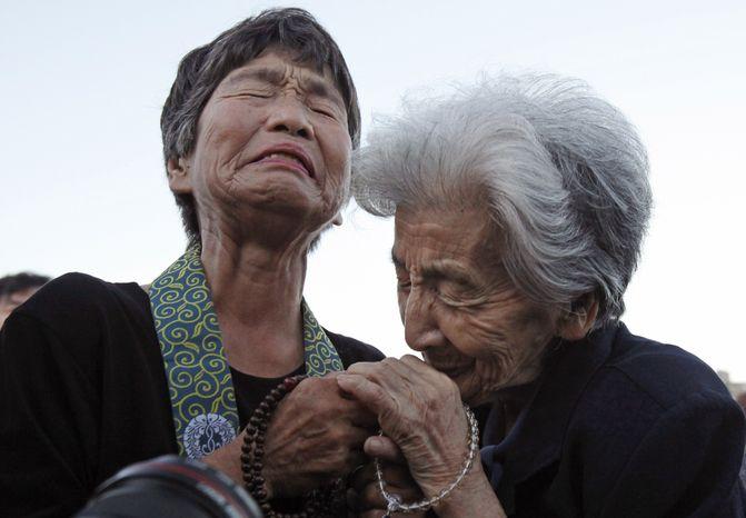 Tsuyuko Nakao, 92, right, and Kinuyo Ikegami, 77, both bereaved family members of the atomic bomb victims, console each other as they pray for the victims in front of the cenotaph at the Peace Memorial Park in Hiroshima, western Japan, Friday, Aug. 6, 2010. Hiroshima marked the 65th anniversary of the the world's first atomic bomb attack that devastated the western Japanese city at the closing days of World War II. (AP Photo/Shuji Kajiyama)
