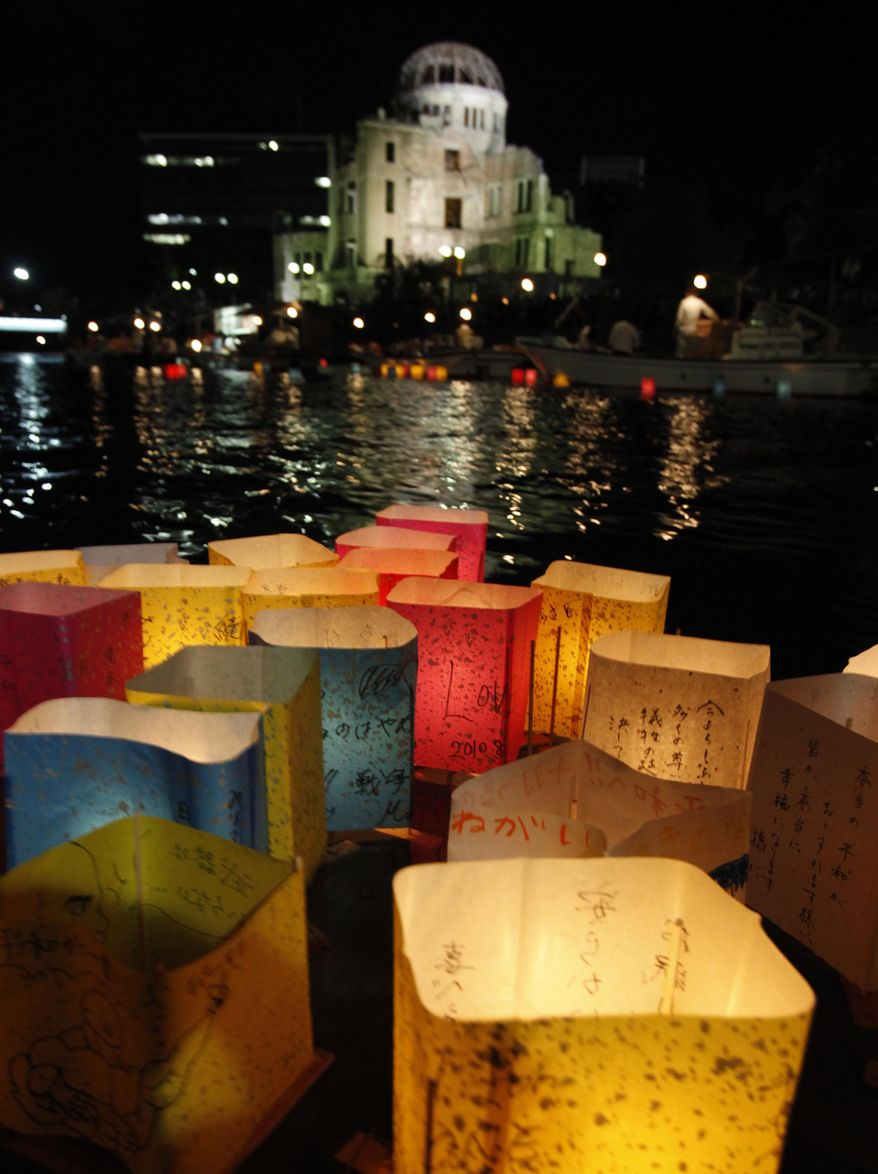With the gutted Atomic Bomb Dome in the background, paper lanterns float on the Motoyasu River for a memorial service of the atomic bomb victims in Hiroshima, western Japan, Friday, Aug. 6, 2010. Hiroshima marks the 65th anniversary of the the world's first atomic bomb attack that devastated the western Japanese city at the closing days of World War II. (AP Photo/Shuji Kajiyama)