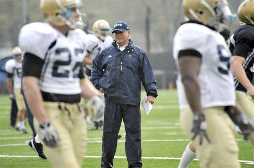 FILE - This April 7, 2010, file photo shows Notre Dame coach Brian Kelly watching his team practice in the rain,  in South Bend, Ind. Kelly has spent nearly seven months as Notre Dame's ambassador. Now comes the toughest part for the coach _ making the Irish a contender again. (AP Photo/Joe Raymond, FIle)