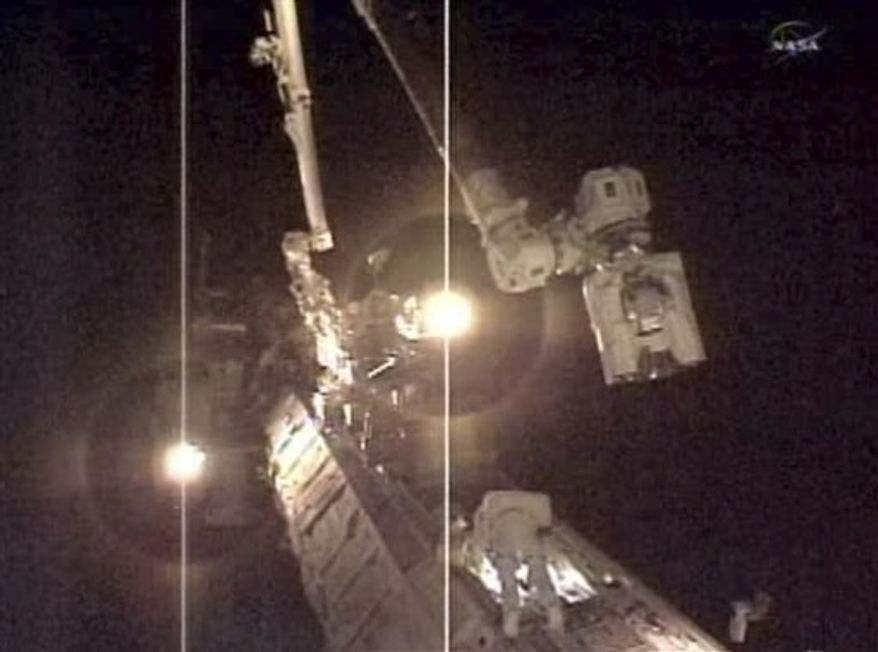 In this photo taken from NASA television, Expedition 24 astronauts work outside the space station, Monday, Aug. 16, 2010. (AP Photo/NASA)