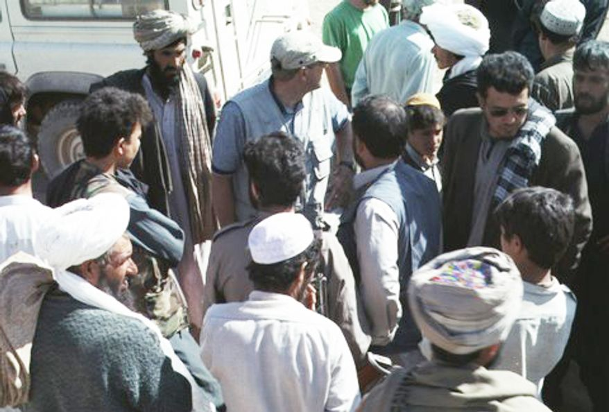 Tom Little (top center in blue shirt with baseball cap), an optometrist and team leader with the International Assistance Mission, joins villagers and other team members in Afghanistan in this undated photo. (AP Photo/Provided by David L. Evans)