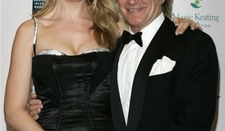 FILE - In this Nov. 30, 2007 file photo, British singer Rod Stewart, right, and his wife Penny Lancaster arrive for the Emeralds & Ivy Ball, to raise money for Cancer Research UK, at Old Billingsgate Market in London. Stewart and Lancaster announced Monday, Aug. 9, 2010 they are expecting their second child - and the 65-year-old rocker's seventh. (AP Photo/Sang Tan, File)