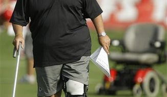 In this July 30, 2010, photo, Kansas City Chiefs offensive coordinator Charlie Weis uses a cane to walk away from his motorized chair during football training camp in St. Joseph, Mo. (AP Photo/Orlin Wagner)