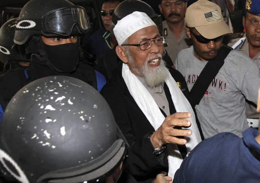 Radical Indonesian cleric Abu Bakar Bashir (center) is escorted by anti-terror police as he arrives at Indonesian police headquarters in Jakarta, Indonesia, on Monday, Aug. 9, 2010. Mr. Bashir, once imprisoned for his links to the terror group behind the Bali bombings, was arrested Monday for alleged involvement with a new militant network. (AP Photo/Irwin Ferdiansyah)