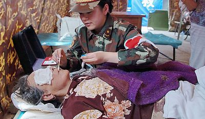 In this photo released by China's Xinhua News Agency, 74-year-old Yang Jinfeng receives medical treatments in a camp in Zhouqu county, in northwest China's Gansu Province, on Monday Aug. 9, 2010. Thirty-five hours after holding herself while her lower body was buried in the rain-triggered mud, Yang Jinfeng was finally rescued Monday morning by an armed police rescue team, Xinhua said. (AP Photo/Xinhua, Gao Jianjun)