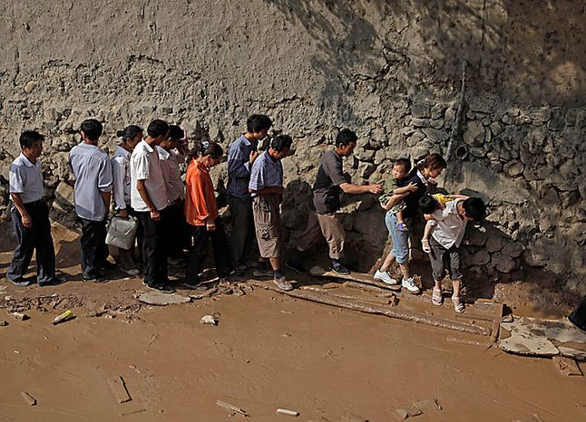 Residents walk in a line at the mudslide-devastated town of Zhouqu in Gannan prefecture in northwestern China's Gansu province on Monday, Aug. 9, 2010. Rescuers dug through mud and wreckage Monday searching for 1,300 people missing after flash floods and landslides struck northwestern China. (AP Photo/Ng Han Guan)