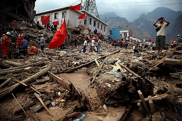 A man takes a picture of the devastated town of Zhouqu in Gannan prefecture in northwestern China's Gansu province on Monday, Aug. 9, 2010. Rescuers dug through mud and wreckage Monday searching for 1,300 people missing after flash floods and landslides struck northwestern China, just one of a series of floods across Asia that have killed hundreds and spread misery to millions more. (AP Photo/Ng Han Guan)