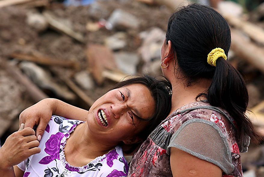 A woman cries for her missing family members after a mudslide triggered by heavy rains in Zhouqu county in northwest China's Gansu province on Monday, Aug. 9, 2010. Rescuers searched Monday for an estimated 1,300 people left missing after rubble-strewn floodwaters tore through a remote corner of northwestern China, just one of a series of flood disasters across Asia that have plunged millions into misery. (AP Photo)