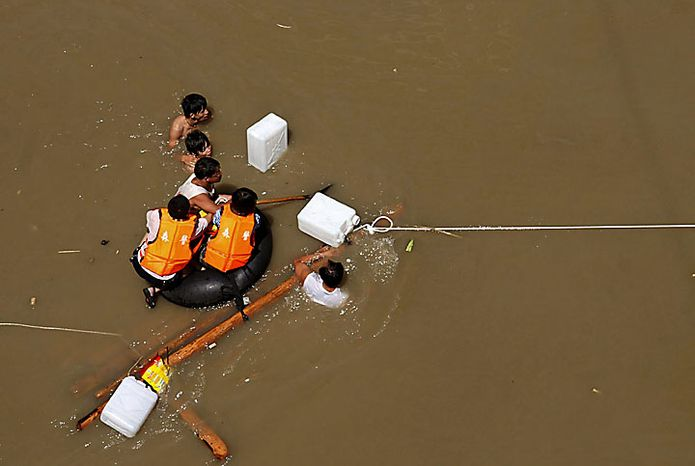 Rescuers clinging to a rope-tied makeshift float search for victims in a flooded area after heavy rains triggered a mudslide in Zhouqu county in northwestern China's Gansu province on Sunday, Aug. 8, 2010. Rescuers searched Monday for an estimated 1,300 people left missing after rubble-strewn floodwaters tore through a remote corner of northwestern China, just one of a series of flood disasters across Asia that have plunged millions into misery. (AP Photo)