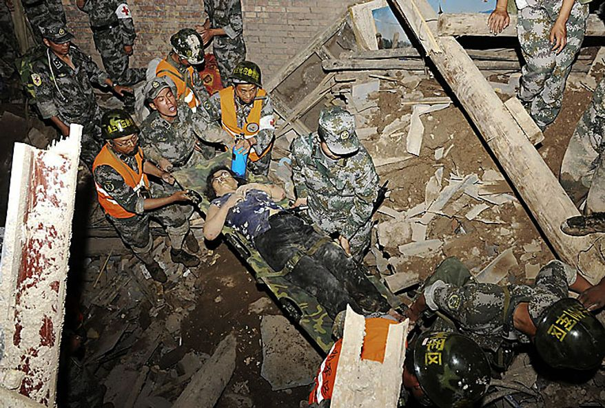Soldiers carry a rescued woman on a stretcher after heavy rains triggered a mudslide in Zhouqu county in northwestern China's Gansu province on Sunday, Aug. 8, 2010. Rescuers searched Monday for an estimated 1,300 people left missing after rubble-strewn floodwaters tore through a remote corner of northwestern China, just one of a series of flood disasters across Asia that have plunged millions into misery. (AP Photo)