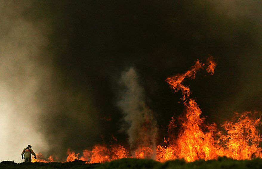 A firefighter works on a fire front on Arada Mountain near Sao Pedro do Sul, Portugal, on Monday, Aug. 9, 2010. Firefighters were continuing to battle raging brush fires on Monday. They say some have been contained but others are still burning out of control. (AP Photo/Francisco Seco)