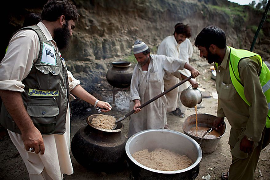 Volunteers of the Falah-e-Insaniyat foundation, the charity wing of the Pakistani militant group Jamaat-ud-Dawa, supervise the cooking of food for flood-affected people in Nowshera in northwest Pakistan on Monday, Aug. 9, 2010. The number of people suffering from the massive floods in Pakistan exceeds 13 million -- more than the combined total of the 2004 Indian Ocean tsunami, the 2005 Kashmir earthquake and the 2010 Haiti earthquake, the United Nations said. (AP Photo/B.K. Bangash)
