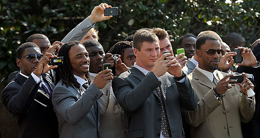 Members of the 2009 Super Bowl-winning New Orleans Saints NFL football team watch as Marine One, carrying President Obama, takes off from the South Lawn of the White House in Washington on Monday, Aug. 9, 2010.  (AP Photo/Susan Walsh)