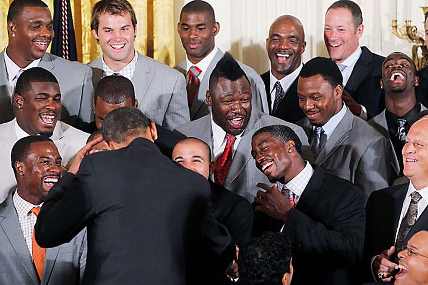 President Obama points to his hair as he greets the Super Bowl-winning New Orleans Saints during a ceremony in the East Room of the White House in Washington, Monday, Aug. 9, 2010. Saints defensive tackle Remi Ayodele, with a Mohawk, is at center. (AP Photo/Charles Dharapak)