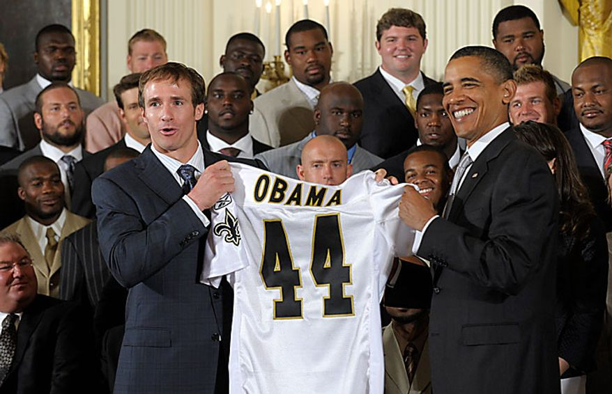 President Obama (right) receives a New Orleans Saints football jersey from Saints quarterback Drew Brees as Mr. Obama honored the Super Bowl-winning Saints on Monday, Aug. 9, 2010, in the East Room of the White House in Washington. (AP Photo/Susan Walsh)