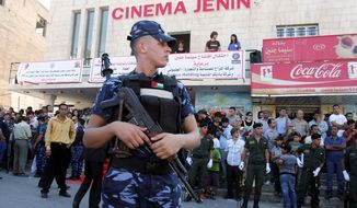 A police officer guards Cinema Jenin as Palestinians gather for its opening. The movie house, a rare commodity in the West Bank, marks a milestone in the shift of Jenin from a hub for Palestinian gunmen to a growing city. (Associated Press)