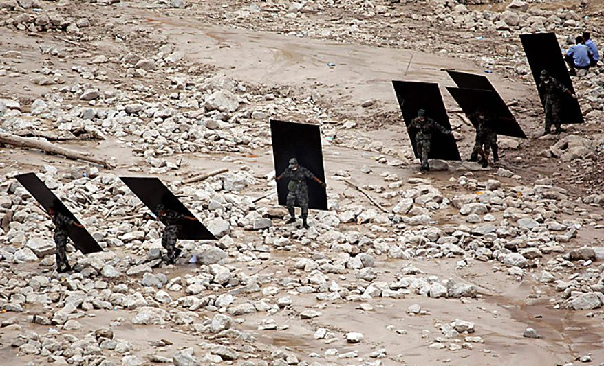 Chinese rescue workers carry wooden boards to create a passable route through soft mud after a mudslide swept into the town of Zhouqu in Gannan prefecture of northwestern China's Gansu province, Tuesday, Aug. 10, 2010. (AP Photo/Ng Han Guan)