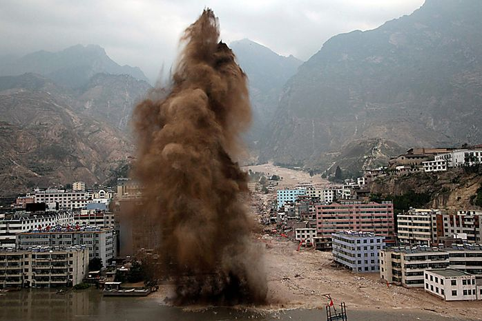 Explosives are set off to clear away debris stemming the flow of a river after a mud slide swept into the town of Zhouqu in Gannan prefecture of northwestern China's Gansu province, Tuesday, Aug. 10, 2010. (AP Photo/Ng Han Guan)