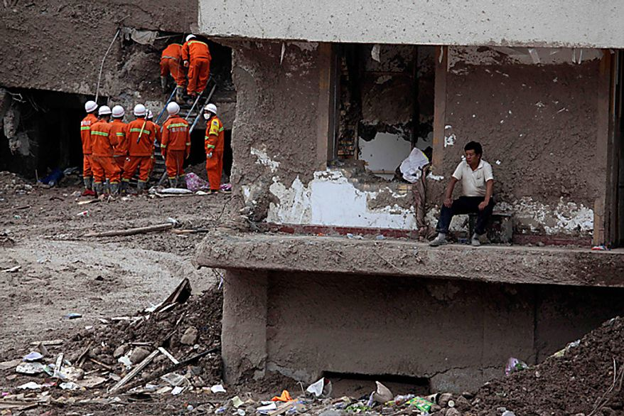 A Chinese man rests near a damaged building as rescue workers search a neighboring building after a mudslide swept into the town of Zhouqu in Gannan prefecture of northwestern China's Gansu province, Tuesday, Aug. 10, 2010. Rescuers in three countries across Asia struggled Tuesday to reach survivors from massive flooding that has afflicted millions of people, as the death toll climbed in the remote Chinese town where hundreds died and more than 1,100 were missing from landslides. (AP Photo/Ng Han Guan)