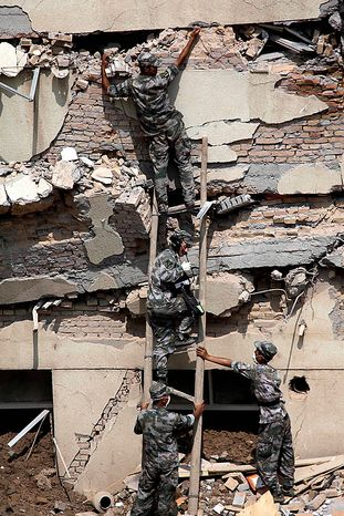 Chinese soldiers use a life detecting device to search for survivors in a building that partially collapsed after Sunday's mud slide swept into the town of Zhouqu in Gannan prefecture of northwestern China's Gansu province, Tuesday, Aug. 10, 2010. Rescuers in three countries across Asia struggled to reach survivors from flooding that has afflicted millions of people. (AP Photo/Ng Han Guan)