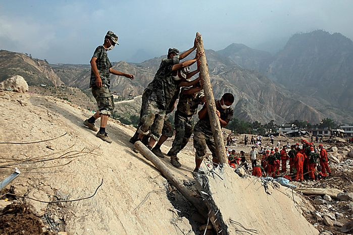 Chinese soldiers attempt to pry open the concrete wall of a building that collapsed after Sunday's mud slide swept into the town of Zhouqu in Gannan prefecture of northwestern China's Gansu province, Tuesday, Aug. 10, 2010. Rescuers in three countries across Asia struggled to reach survivors from flooding that has afflicted millions of people. (AP Photo/Ng Han Guan)