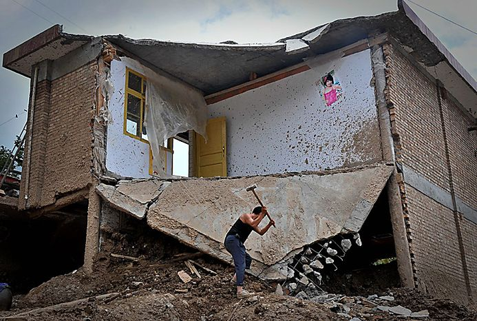 In this photo taken on Aug. 9, 2010, a Chinese man uses a hammer to knock his damaged house down in the mudslide-hit town of Zhouqu in Gannan prefecture of northwestern China's Gansu province. Rescuers in three countries across Asia struggled Tuesday to reach survivors from massive flooding that has afflicted millions of people, as the death toll climbed in a remote Chinese town where hundreds died and more than 1,100 were missing from landslides. (AP Photo)