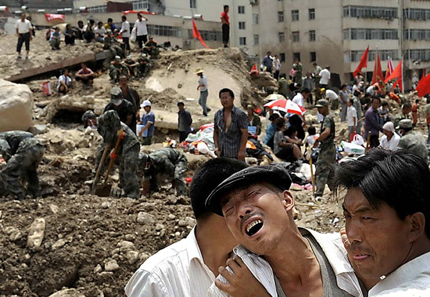 A Chinese man grieves over his loss while being comforted by others after a mudslide swept into the town of Zhouqu in Gannan prefecture of northwestern China's Gansu province, Tuesday, Aug. 10, 2010. Rescuers in three countries across Asia struggled Tuesday to reach survivors from massive flooding that has afflicted millions of people, as the death toll climbed in a remote Chinese town where hundreds died and more than 1,100 were missing from landslides. (AP Photo)