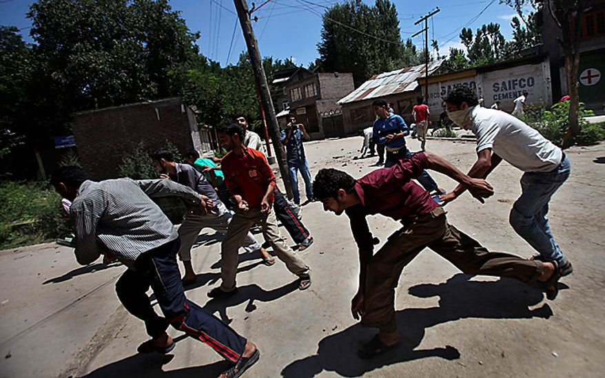 Kashmiri Muslim protestors run for cover as Indian police officers chase them away during an anti-India procession in Chadoora, about 25 kilometers (15 miles) south of Srinagar, India, Tuesday, Aug. 10, 2010. India's Prime Minister Manmohan Singh on Tuesday appealed for calm in Indian-controlled Kashmir as thousands of local Muslims marched and offered special prayers in open fields to honor those killed in recent civil unrest. (AP Photo/Altaf Qadri)