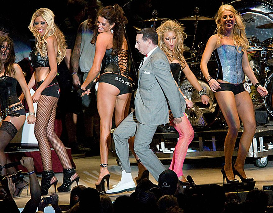 """Comedian Paul Reubens, better known as Pee Wee Herman, does his """"Tequila Dance"""" on stage Monday, Aug. 9, 2010, at the Buffalo Chip Campground with the contestants of the Miss Buffalo Chip Contest. The 70th Annual Sturgis Motorcycle Rally is rocking out with as many as 600,000 bikers visiting the small western South Dakota town this week. (AP Photo/Steve McEnroe)"""