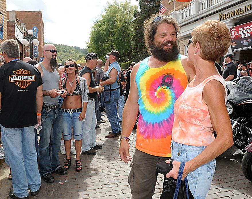 """Rupert Boneham, a favorite on the reality TV series """"Survivor,"""" chats with friends and poses for photos on Main Street in Deadwood, S.D. on Monday, Aug. 9, 2010 before rolling out on the 3rd Annual Legends Ride charity event, which is part of the 70th Annnual Sturgis Motorcycle Rally. (AP Photo/Steve McEnroe)"""