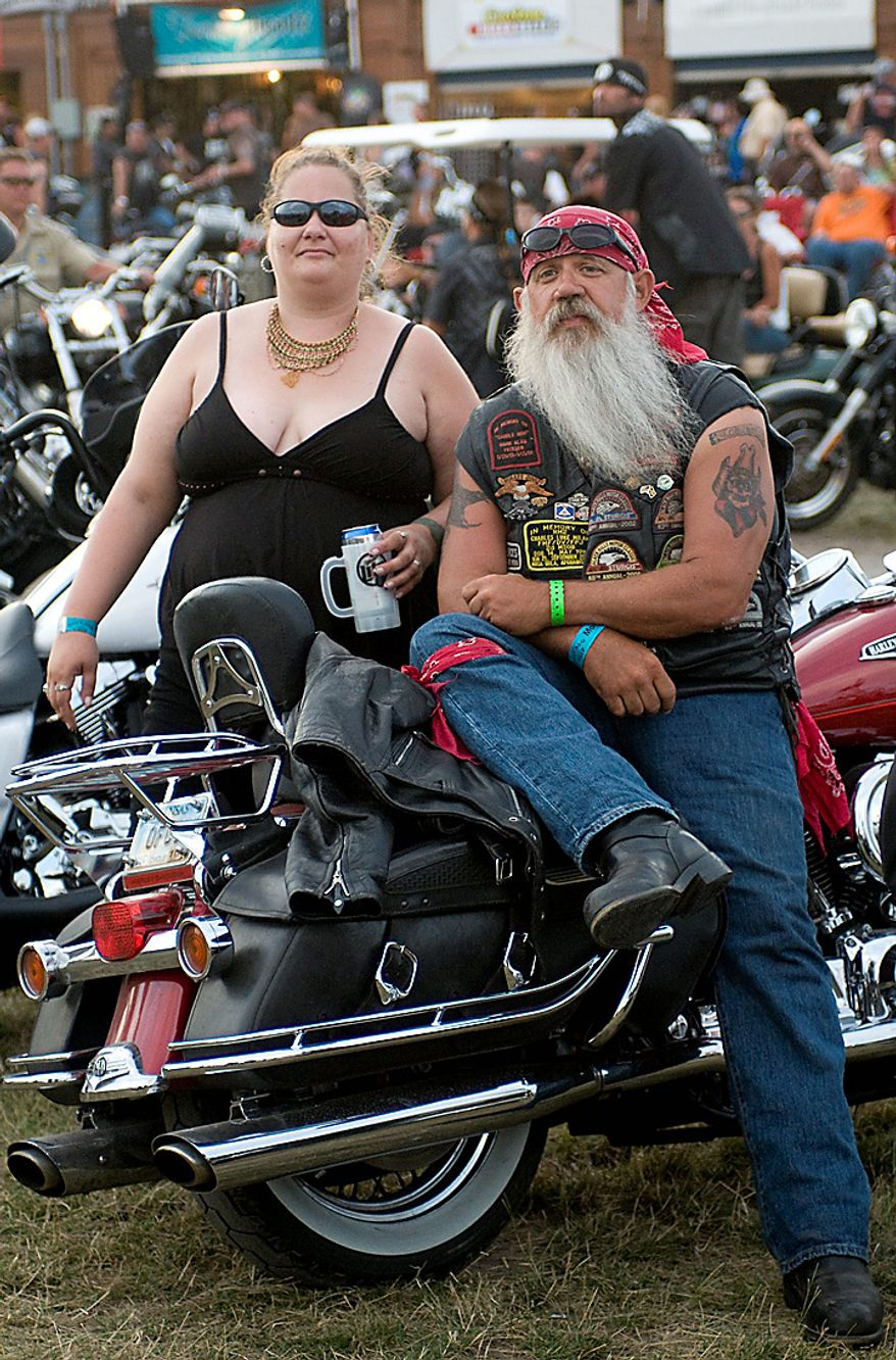 Jonnetta Young, 35, of Whitewood, SD and Ron Ulmer, 49, of Newton, KS relax on Ulmer's Harley-Davidson motorcycle as they watch the concert at the Buffalo Chip Campground Monday, Aug. 9,. 2010 at the 70th Annual Sturgis Motorcycle Rally in the Black Hills of South Dakota. (AP Photo/Steve McEnroe)