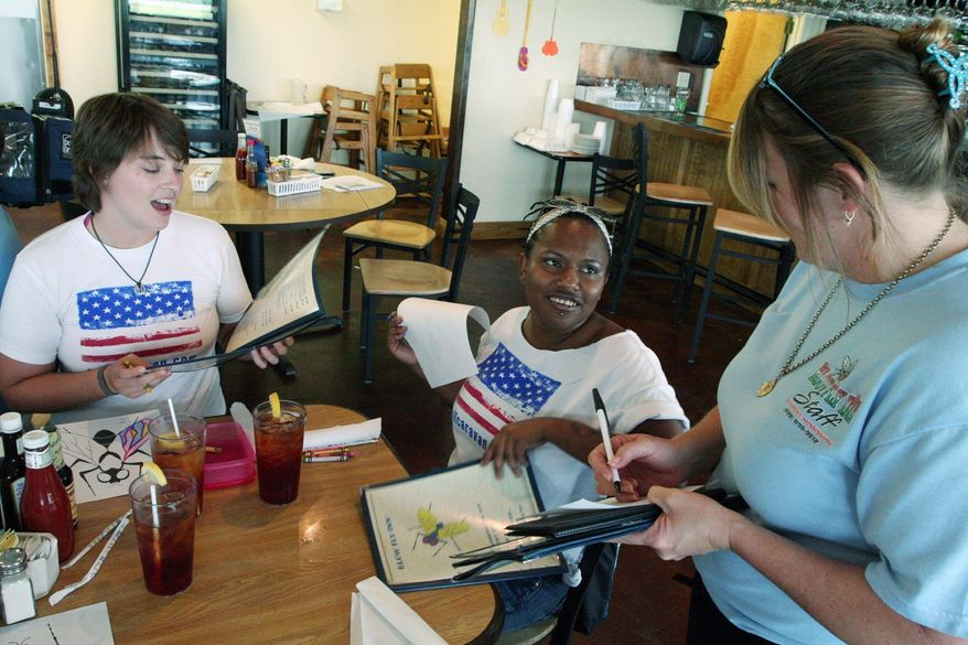 """STEPHEN DINAN/THE WASHINGTON TIMES A waitress at Blow-Fly Inn in Gulfport, Miss., takes orders from two members of the """"Spending Caravan."""" The group is traveling along the coast from Bay St. Louis, Miss., to Panama City, Fla., with the sole purpose of spending money to garner attention for the region's businesses."""