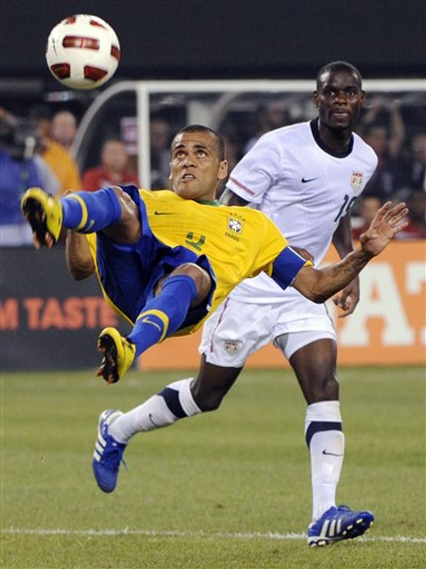 Brazil defender Dani Alves, left, goes up for a bicycle kick as U.S. midfielder Maurice Edu looks on during the second half of an exhibition soccer match Tuesday, Aug. 10, 2010, at New Meadowands Stadium in East Rutherford, N.J. Brazil won 2-0. (AP Photo/Bill Kostroun)