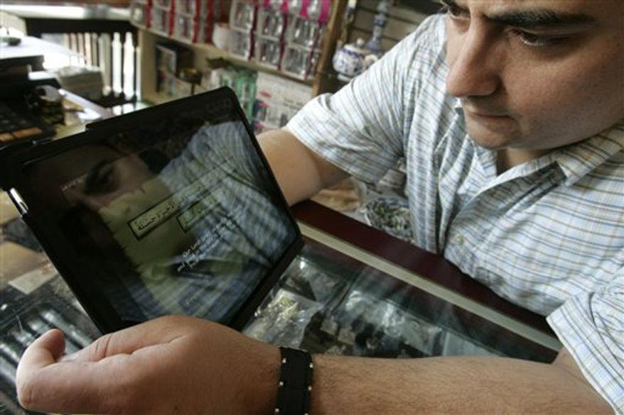 Jim Otun of Fairfield, N.J. is reflected in his IPad as he reads a dua from the Quran at Zinnur Books in Paterson, N.J., Thursday, Aug. 5, 2010. Many Muslims across the country are using new technologies to help them in their islamic beliefs. (AP Photo/Rich Schultz)
