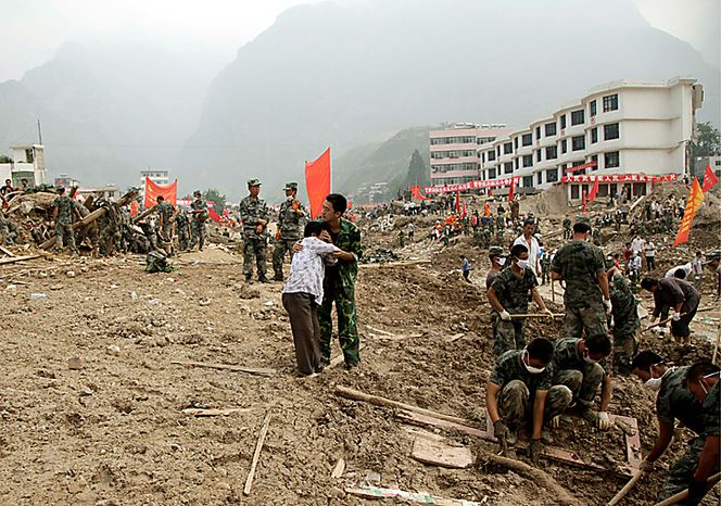 A man consoles a woman grieving for her loss as rescue workers search for victims after a mudslide swept into the town of Zhouqu in Gannan prefecture of northwestern China's Gansu province, Wednesday, Aug. 11, 2010. (AP Photo/Ng Han Guan)