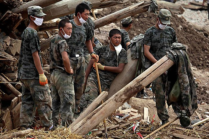Chinese soldiers rest from efforts to recover bodies after a mudslide swept into the town of Zhouqu in Gannan prefecture of northwestern China's Gansu province, Wednesday, Aug. 11, 2010.  Heavy rains Wednesday lashed a remote section of northwestern China as the death toll from weekend flooding that triggered massive landslides jumped to more than 1,000 and the hopes of finding more survivors faded.  (AP Photo/Ng Han Guan)