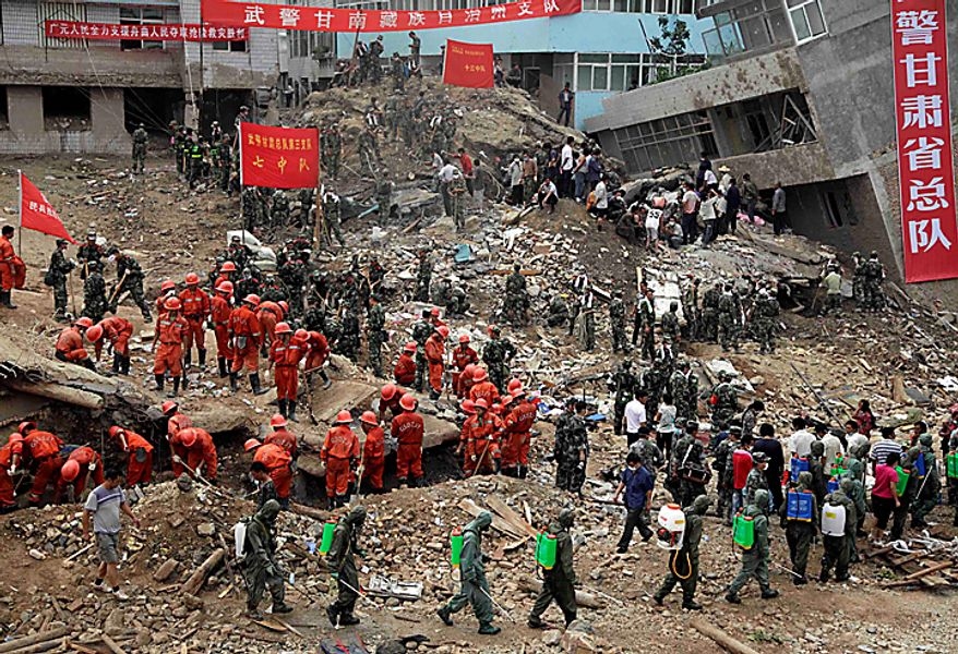 Rescue workers continue to dig for victims of a mudslide that swept into the town of Zhouqu in Gannan prefecture of northwestern China's Gansu province, Wednesday, Aug. 11, 2010.  Heavy rains Wednesday lashed a remote section of northwestern China as the death toll from weekend flooding that triggered massive landslides jumped to more than 1,000 and the hopes of finding more survivors faded.  (AP Photo/Ng Han Guan)