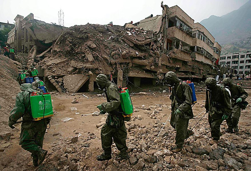 Chinese soldiers disinfect the mudslide-hit town of Zhouqu in Gannan prefecture of northwestern China's Gansu province, Wednesday, Aug. 11, 2010. Heavy rains Wednesday lashed a remote section of northwestern China where weekend flooding killed at least 702 people, as hopes of finding more survivors faded and crews worked to stave off outbreaks of disease.  (AP Photo)