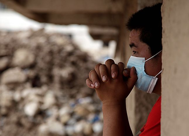 A man wearing a mask to protect from the smell looks over an area destroyed by a mud slide swept that into the town of Zhouqu in Gannan prefecture of northwestern China's Gansu province, Wednesday, Aug. 11, 2010. (AP Photo/Ng Han Guan)