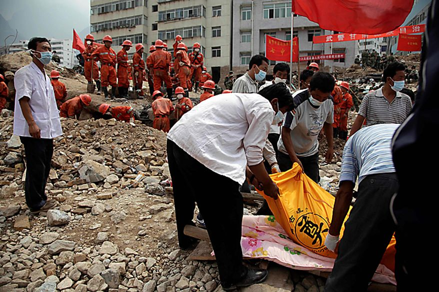 Residents place a body on a stretcher near rescue workers digging for more bodies after a mudslide swept into the town of Zhouqu in Gannan prefecture of northwestern China's Gansu province, Wednesday, Aug. 11, 2010.  Heavy rains Wednesday lashed a remote section of northwestern China as the death toll from weekend flooding that triggered massive landslides jumped to more than 1,000 and the hopes of finding more survivors faded.  (AP Photo/Ng Han Guan)