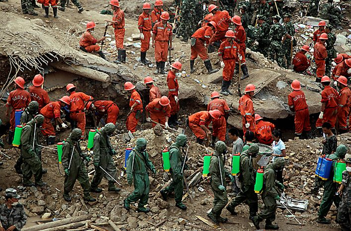 Rescue workers search for victims as a disinfectant crew spays the area after a mudslide swept through the town of Zhouqu in Gannan prefecture of northwestern China's Gansu province, Wednesday, Aug. 11, 2010. Entire communities in Gansu province's Zhouqu district were swallowed up when the debris-choked Bailong River jumped its banks Sunday, releasing wave after wave of mud and rubble-strewn water.  (AP Photo/Ng Han Guan)