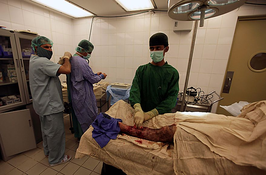 In this Saturday, Aug. 7, 2010 photo, Afghan army doctors and medics prepare for emergency surgery on a wounded Afghan soldier, at Kandahar Regional Military Hospital, KRMH, inside Camp Hero, Kandahar province, southern Afghanistan. The names of the Afghan doctors are withheld for their protection. A U.S Air Force  Medical Training Advisory Group, or MTAG team, comprised of 12 medical professionals, is assigned to the Afghan military hospital, and are tasked with providing transitional guidance to local medical workers, who treat Afghan soldiers, civilians, and occasionally insurgents. (AP Photo/Brennan Linsley)