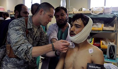 U.S Air Force Physician-Mentor Capt. Michael Hampton, of the Medical Training Advisory Group, or MTAG, stands with an Afghan doctor discussing the treatment of an Afghan Army soldier with a gunshot wound to the neck, at Kandahar Regional Military Hospital, KRMH, inside Camp Hero, Kandahar province, southern Afghanistan, Sunday, Aug. 8, 2010. The names of the Afghan doctors are withheld for their protection. The MTAG team, comprised of 12 U.S. Air Force medical professionals, is assigned to the Afghan military hospital, and are tasked with providing transitional guidance to local medical workers, who treat Afghan soldiers, civilians, and occasionally insurgents. (AP Photo/Brennan Linsley)
