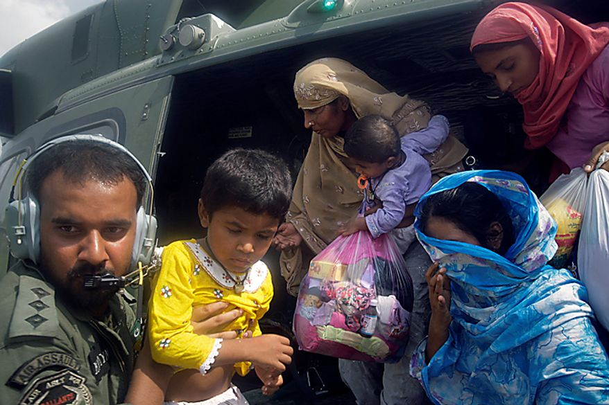 A crew member of a Pakistan  army helicopter helps villagers to get off after being rescued from a flood-hit area in Basera near Muzaffargarh, in central Pakistan on Wednesday, Aug. 11, 2010. Pakistan estimates 13.8 million people are affected by the floods and will need short-term aid or long-term assistance to recover. (AP Photo/K.M. Chaudary)