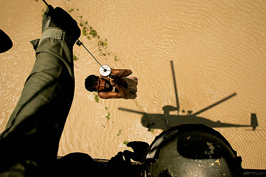 A villager is rescued by a Pakistan's Navy helicopter from flooded area of Ghaus Pur near Sukkur, in Pakistan's Sindh province, Wednesday, Aug. 11, 2010.  Pakistan's President Asif Ali Zardari returned home to a storm of criticism after visiting Europe as his country was gripped by the worst floods in its history. His arrival Tuesday came as thousands of people fled a major city in central Pakistan as rivers threatened to submerge the area. (AP Photo/Shakil Adil)